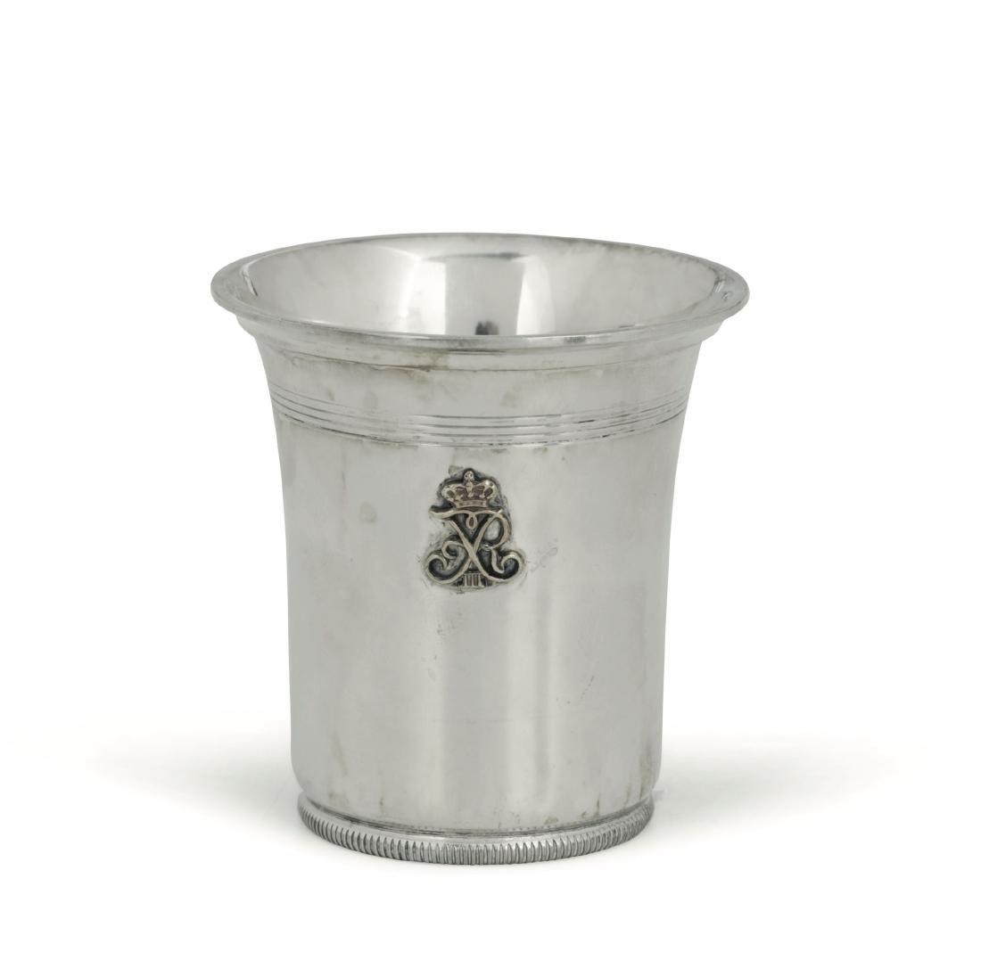 A glass in embossed and chiselled silver with a crowned