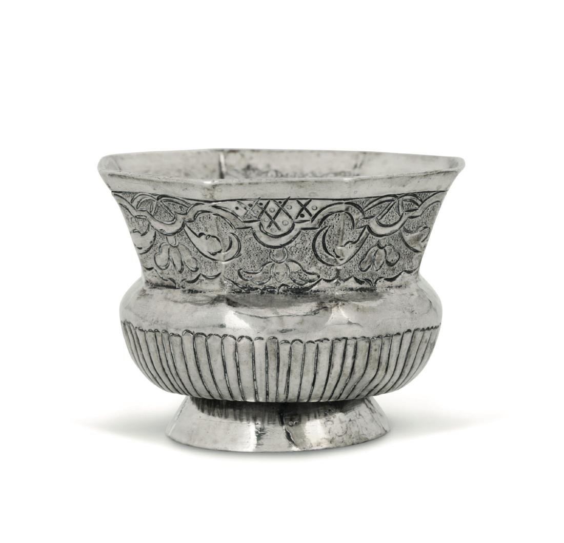 A small cup in embossed and chiselled silver with a