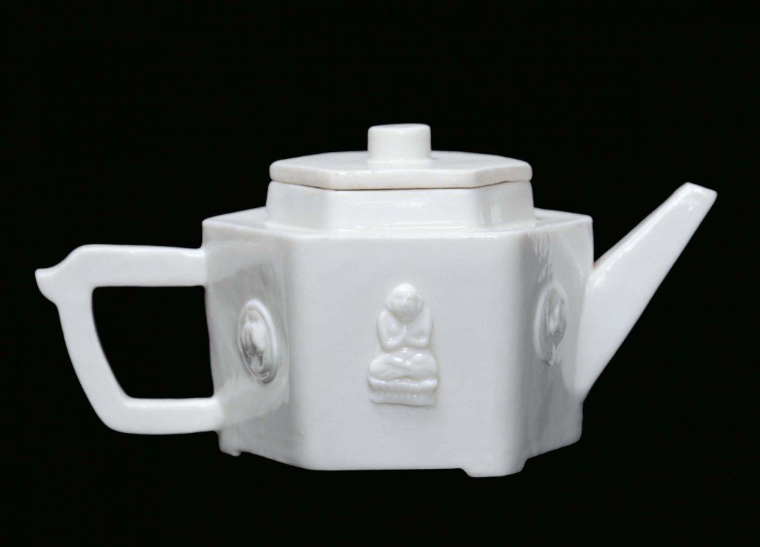 A Blanc de Chine porcelain teapot with relief Buddha an