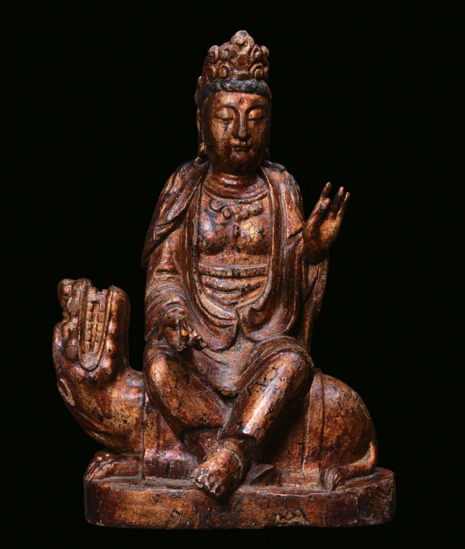 A polychrome and gilt figure of  Guanyin sitting on a P