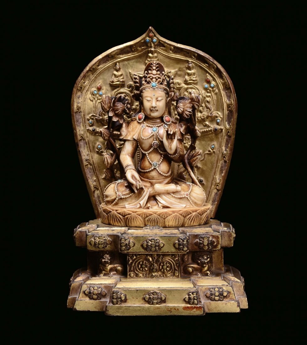 A sculpted ivory figure of Buddha sitting on a gilt bro