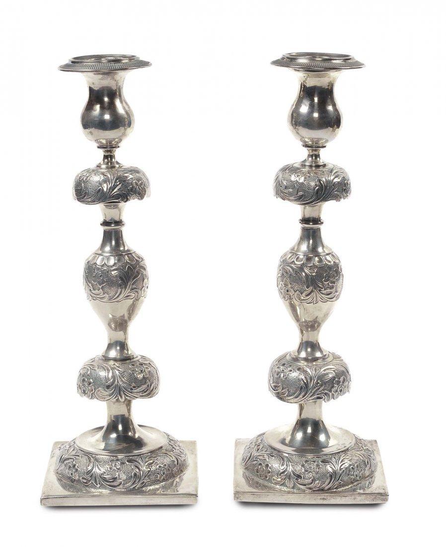 Coppia di candelieri in argento sbalzato e cesellato,