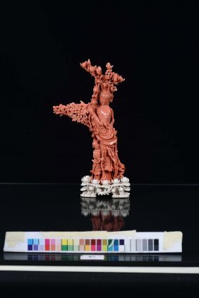 A red coral figure of Guanyin with girl and blooming