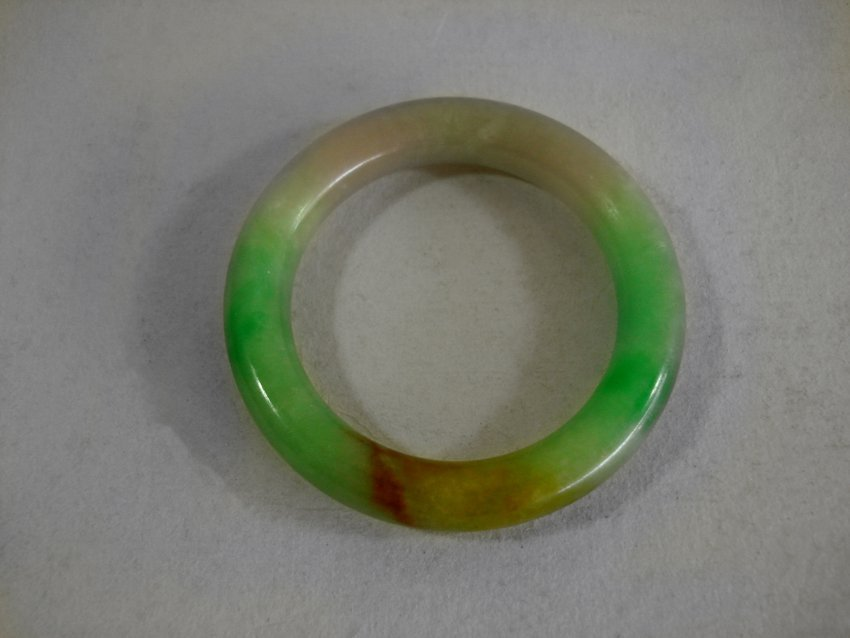 AN CHINESE GREEN WHITE AND RED JADE BRACELET.
