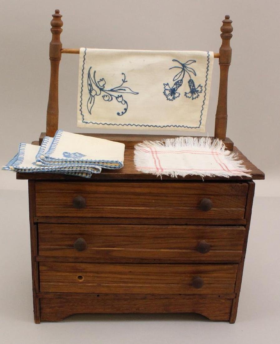ANTIQUE DOLL SIZE OAK CHEST OF DRAWERS WITH LINENS.