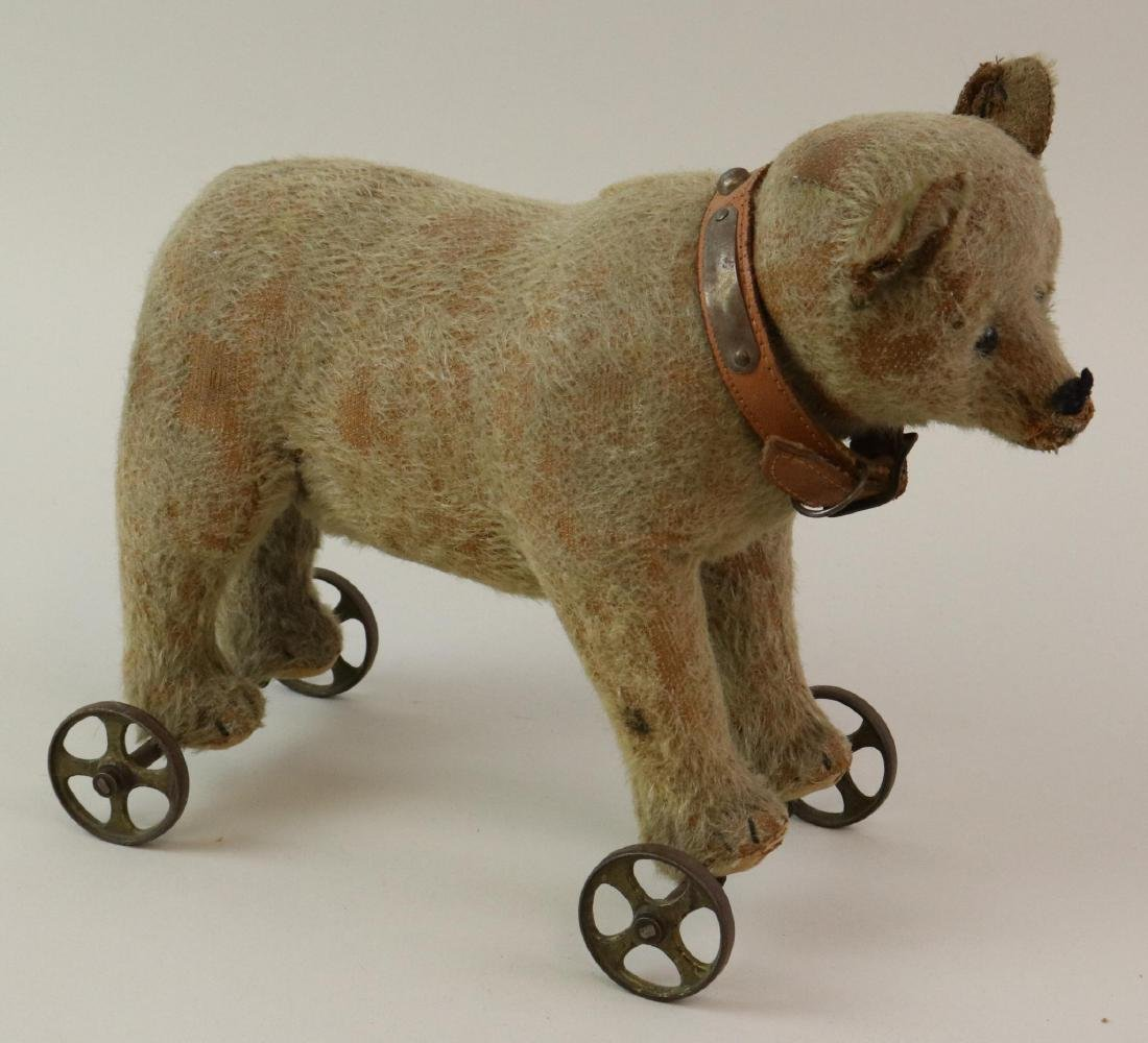 """11"""" L. UNMARKED ANTIQUE MOHAIR BEAR ON WHEELED BASE."""
