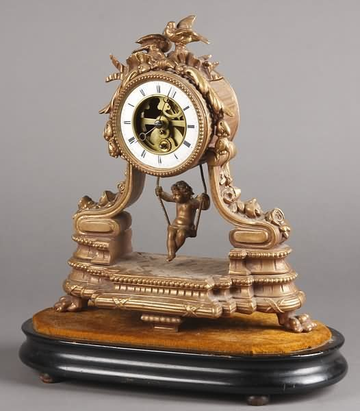 1004: French Swinging Doll Clock on Wooden Base