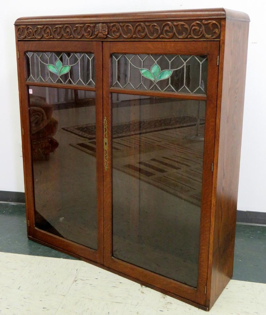 AESTHETIC CARVED OAK DOUBLE-DOOR LEADED GLASS BOOKCASE.