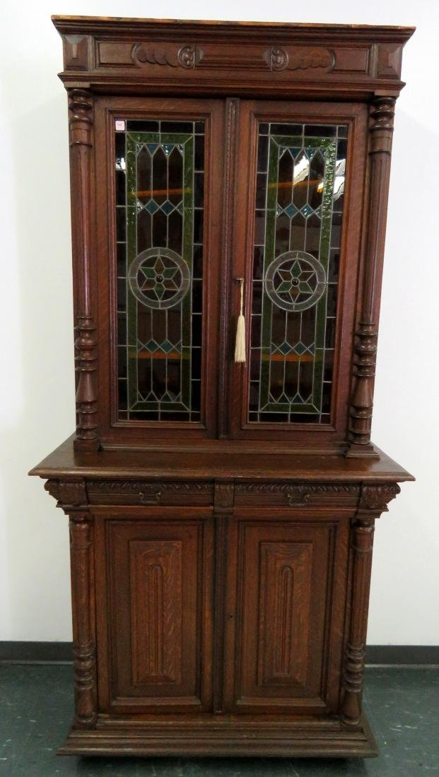 RENAISSANCE STYLE CARVED OAK CABINET WITH LEADED GLASS