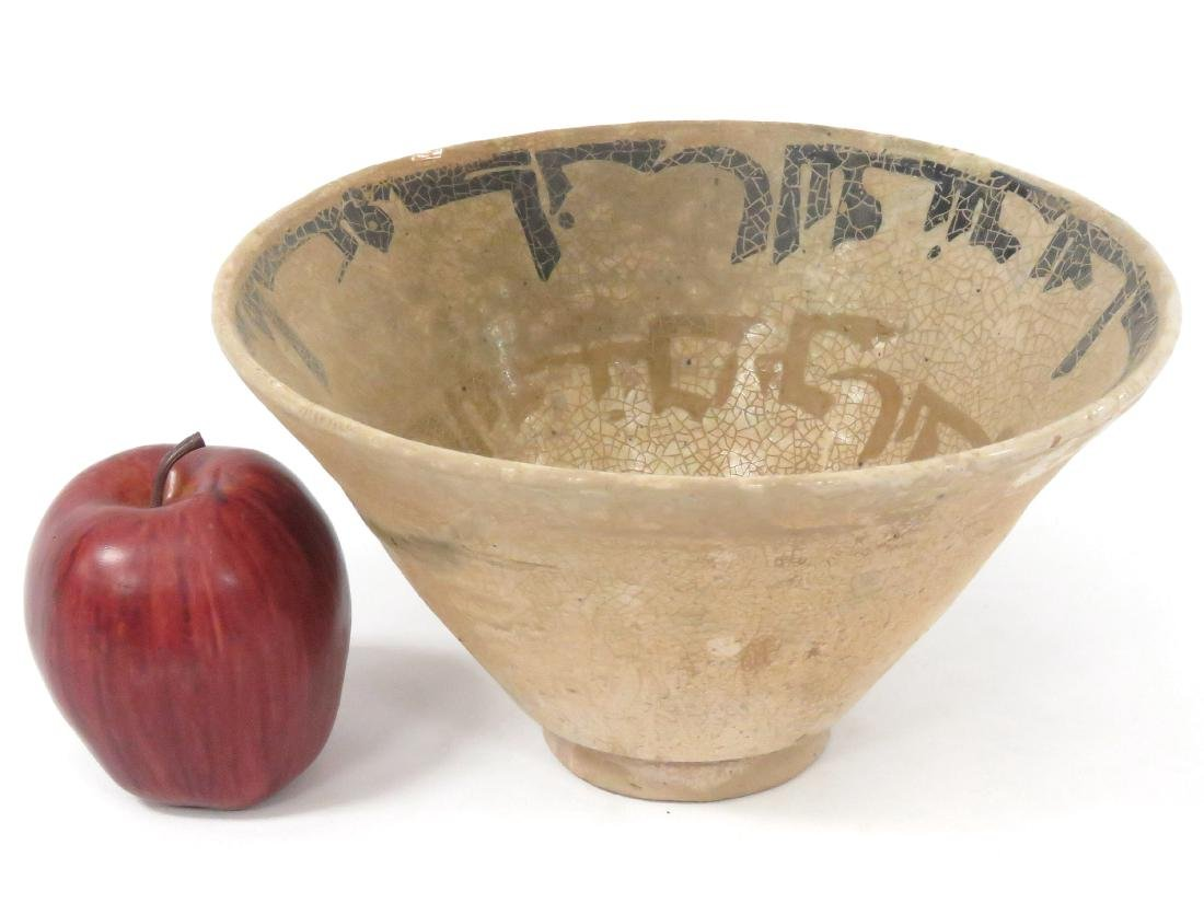 ISLAMIC DECORATED POTTERY BOWL WITH KUFIC SCRIPT.