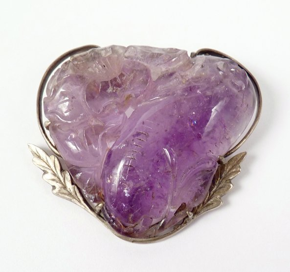 2: An Arts and Crafts carved amethyst brooch, c.1920, a