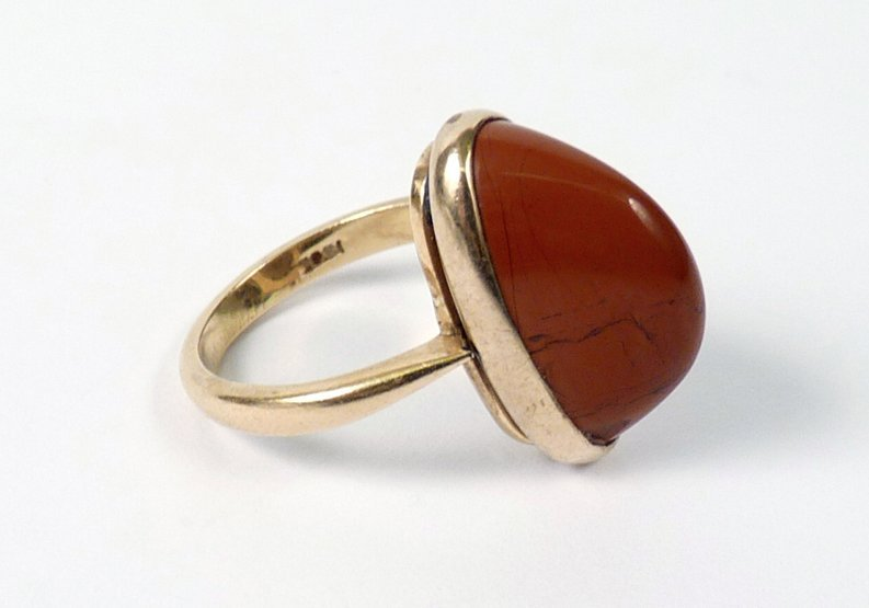 12: A single stone poppy jasper ring, an oval high cabo