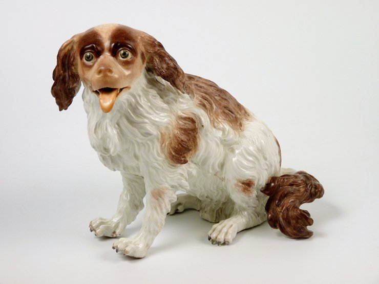 A German porcelain Model of a seated spaniel,  after a