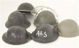 A collection of metal tin helmets, to include World War