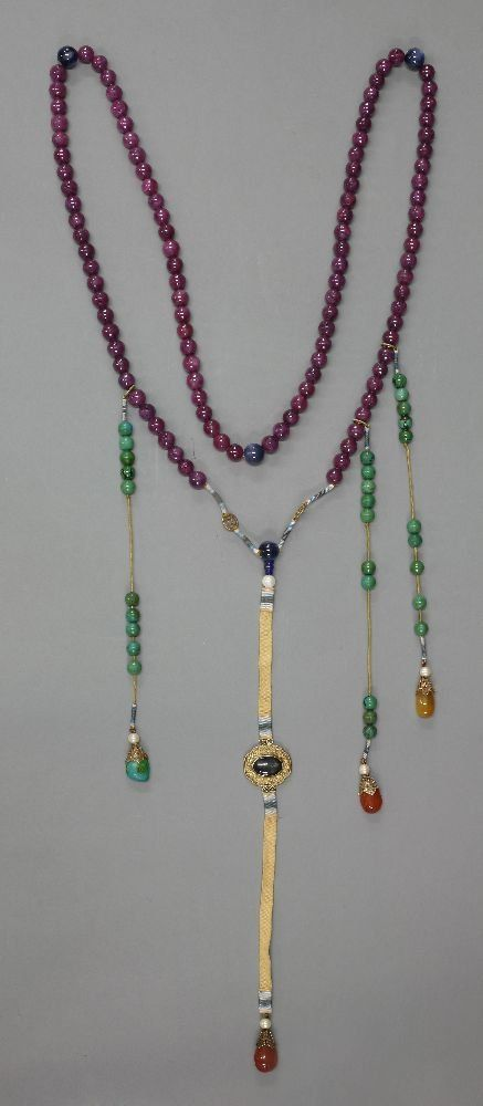 A string of beads, in various stones including ruby,
