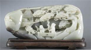 A carved celadon and grey jade sculpture.