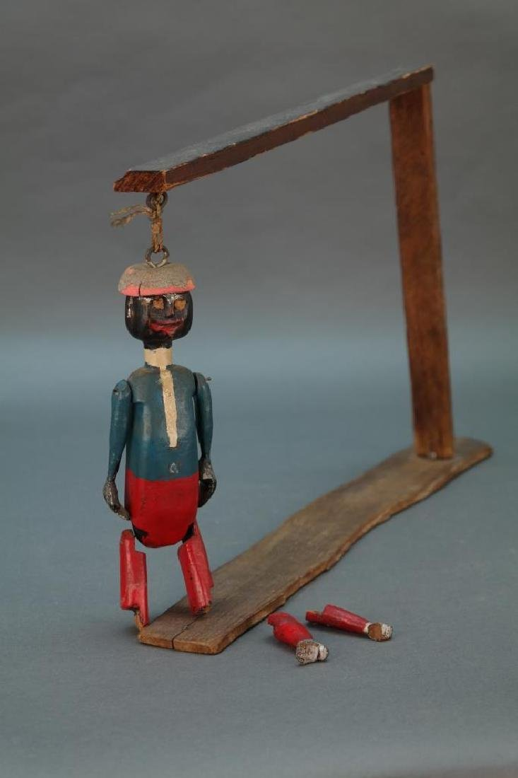 Dancing minstrel on wooden rack.