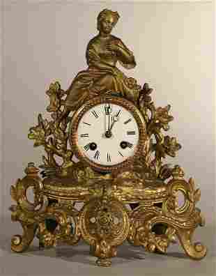 Gilt metal mantle clock, with lady sitting on top