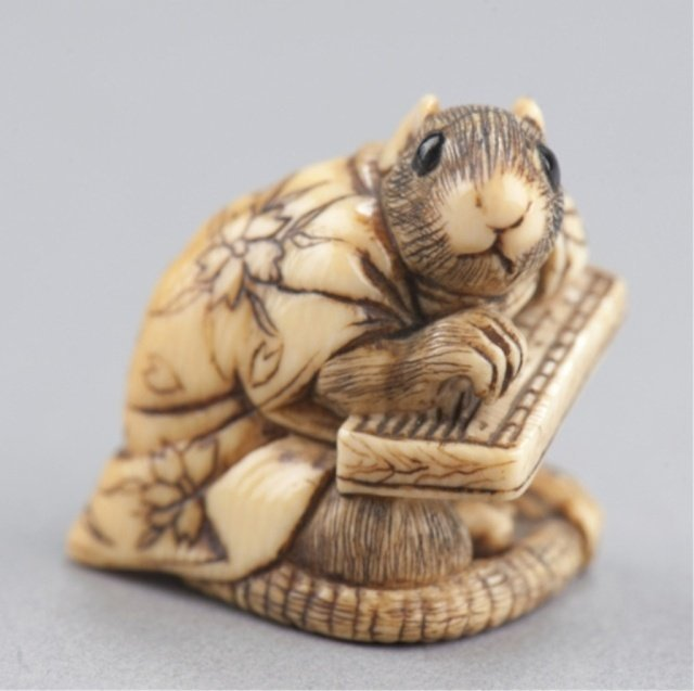 8: An ivory netsuke of a rat in gown.