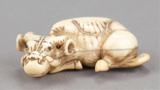 11: An ivory netsuke of a recumbent ox.
