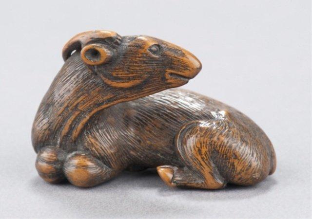12: A wood netsuke of a recumbent goat.