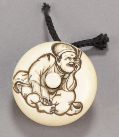 19: An ivory manju of a Noh play prompter.