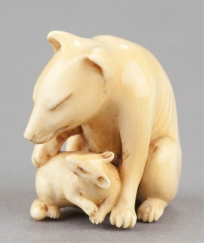 21: An ivory netsuke of a fox and her cub.