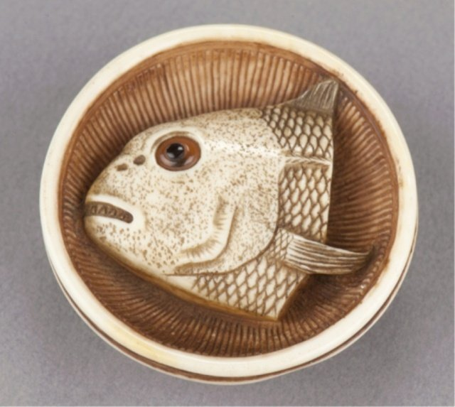 23: An ivory netsuke of a fish head in a bowl.