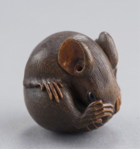 A wood netsuke of a coiled rat.
