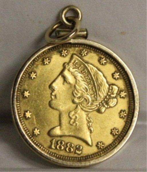 1882 5 dollar gold coin in gold setting.