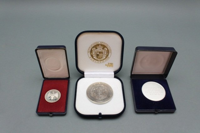 3 silver medals in boxes.