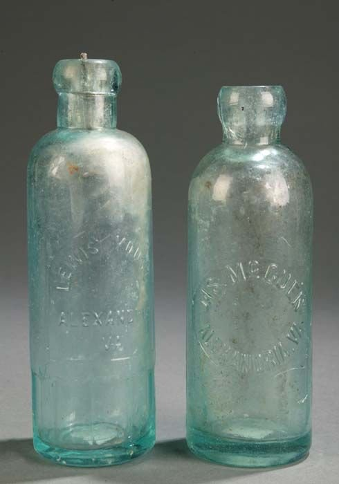 1009: Pair of green pressed glass bottles, one stamped