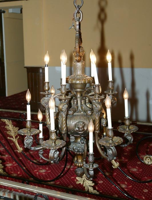 3563: Heavy cast brass 18 arm chandelier with heads of