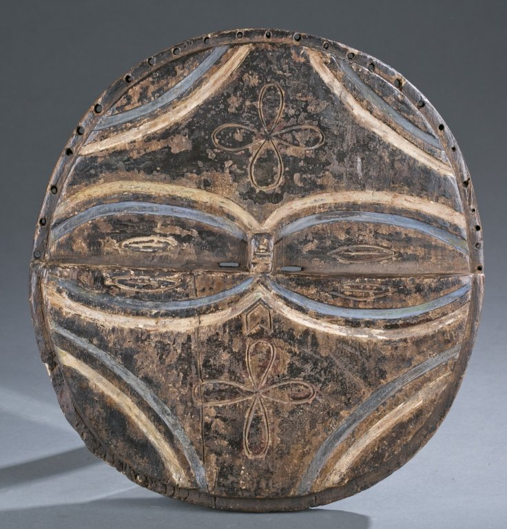 Round wood mask with oval shaped eyes.