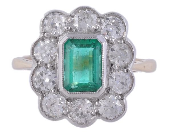 An emerald and diamond cluster ring,  the central