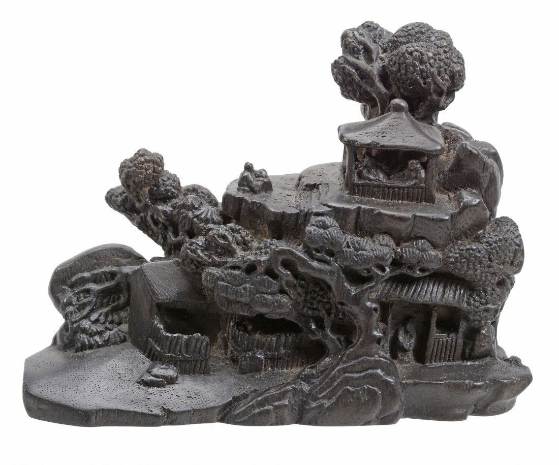 A black wood carving of a miniature landscape