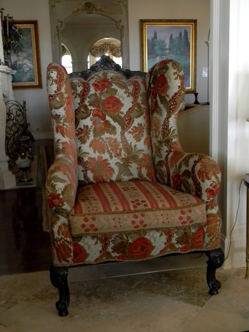 Overstuffed wing chair with velvet upholstery.