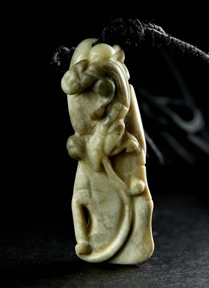 A CHICKEN BONE WHITE JADE PENDANT CARVED DRAGON