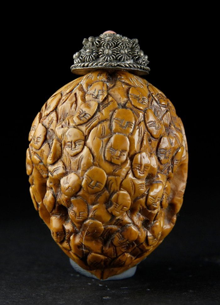 A QING PERIOD NUT CARVED 'LOHAN' SNUFF BOTTLE