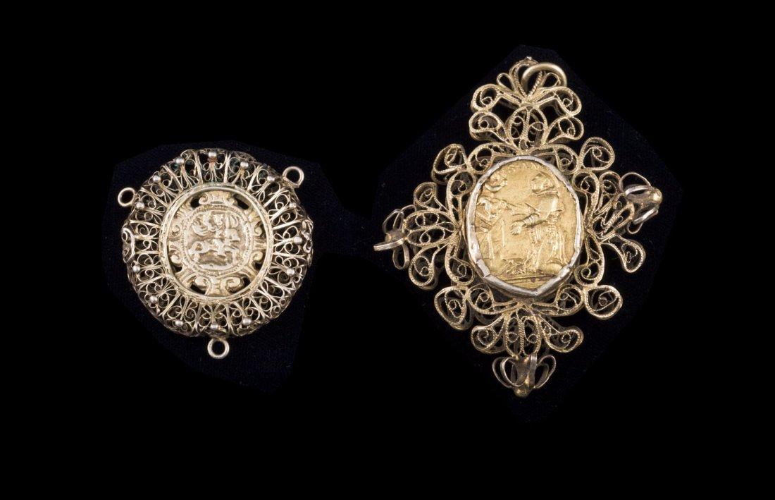 Deux pendentifs en argent doré filigrannés à décor de
