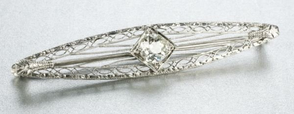 932: A 14K WHITE GOLD AND DIAMOND BAR BROOCH.