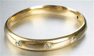 A 14K YELLOW GOLD AND DIAMOND BANGLE BRACELET.