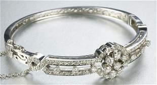 A 14K WHITE GOLD AND DIAMOND BANGLE BRACELET.