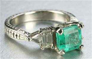 A WHITE GOLD, EMERALD AND DIAMOND RING.