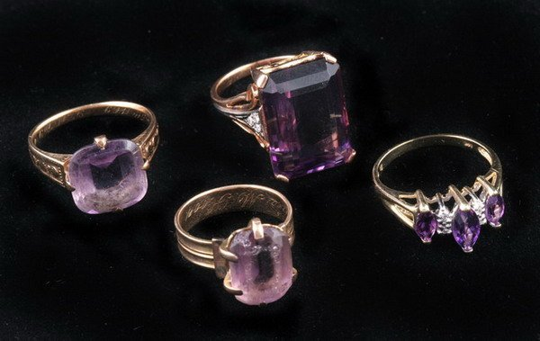 1069: FOUR YELLOW GOLD AND AMETHYST RINGS,