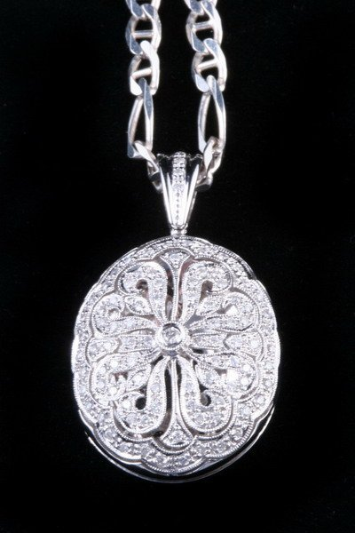 1152: 14K WHITE GOLD AND DIAMOND LOCKET ON STERLING SIL