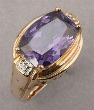 A YELLOW GOLD AND AMETHYST RING. Center
