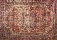 617: AN ANTIQUE PERSIAN MASHAD RUG