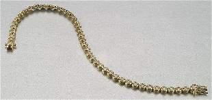 A 14K YELLOW GOLD AND DIAMOND BRACELET,