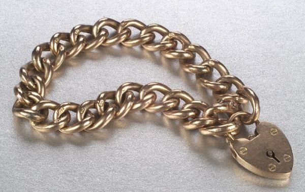 669: A 9K YELLOW GOLD BRACELET AND CHARM. Of
